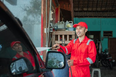 A car cleaner wearing a red uniform and a standing hat sprays water using a hose to the car