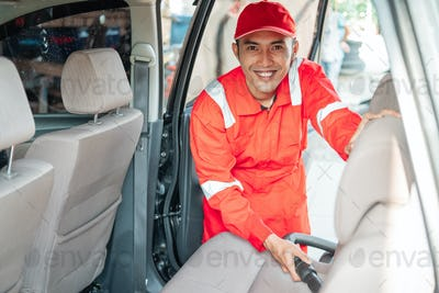The male car cleaner wears a smiling red uniform while cleaning the vacuum cleaner seat
