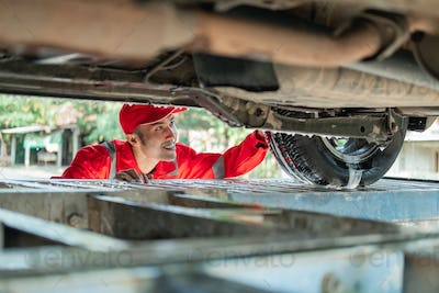 male car cleaner wearing the red uniform looks under the car while washing the car