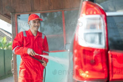 male car cleaner wearing a red uniform and a hat sprays water on the car
