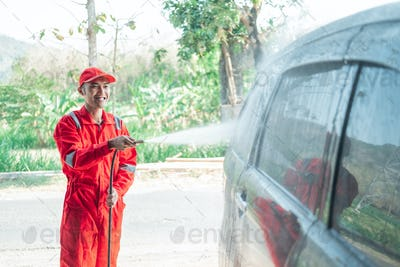 Asian male car cleaner wearing a red uniform and a hat sprays water using a hose onto the car