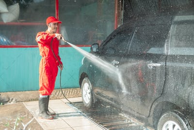 Asian male car cleaner wearing red uniform sprays water while washing the car