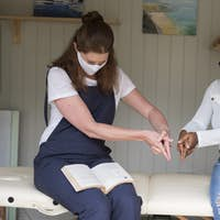 Woman and female therapist in face masks, hands steepled, using a book.