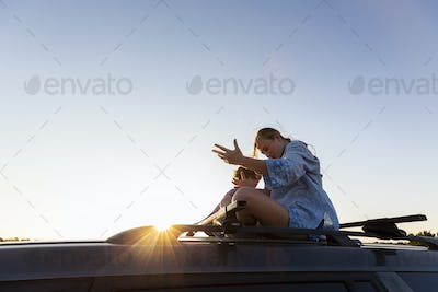 Teenage girl and her younger brother  on top of SUV on desert road, Galisteo Basin, Santa Fe, NM.