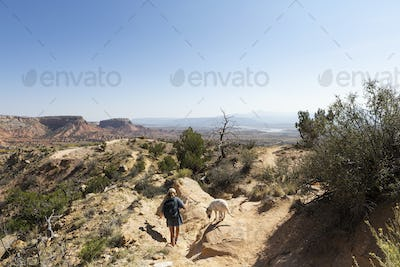 Teenage girl and her retriever dog hiking on a trail through a protected canyon landscape