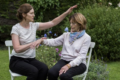 Reiki therapist with a client in a therapy session touching meridian points on the body.