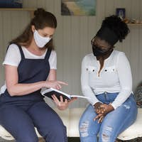 Woman and female therapist in face masks during a therapy session.