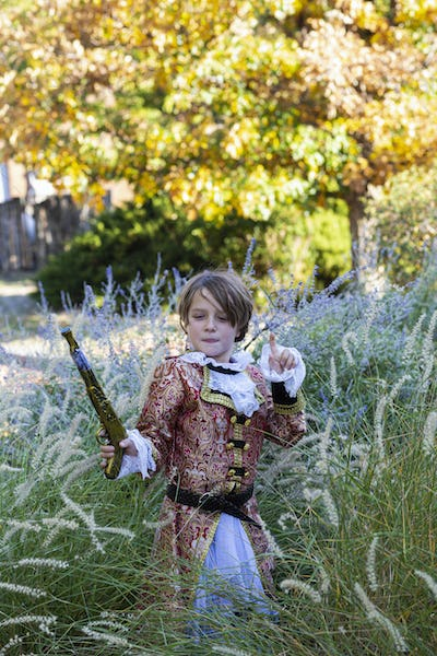 Young boy dressed as a pirate holding long pistol.