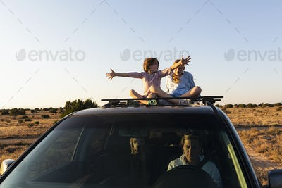Teenage girl and her younger brother  on top of SUV on desert road