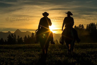Two cowboys riding across grassland with mountains in background, early morning