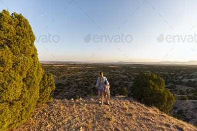 Teenage girl embracing her younger brother in the Galisteo Basin, Santa Fe, NM.