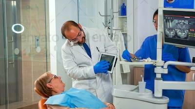 Dentist in dental office examining x-ray image on tablet