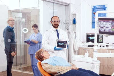 Stomatolog holding x-ray of senior woman sitting on orange chair