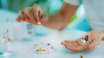 Female patient counting pills. Medicine non-adherence.