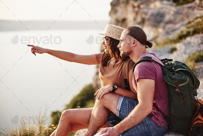 Young couple resting from walking at the edge of the mountain. Wonders how far other coast is it