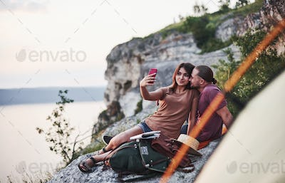 Let's take selfie. Two person sitting on the rock and watching gorgeous nature
