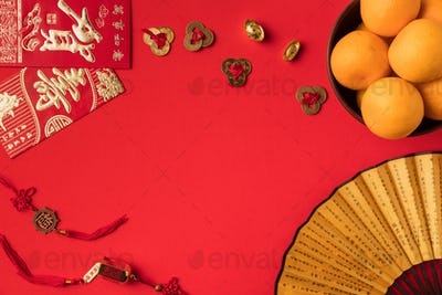 top view of fan, greeting cards, oriental decorations and tangerines isolated on red