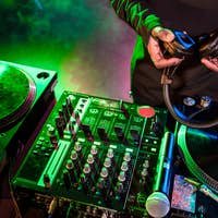 cropped view of club DJ hands holding headphones over sound mixer