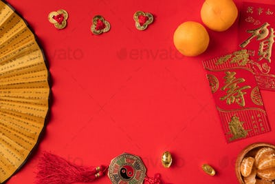 top view of oriental decorations and tangerines isolated on red