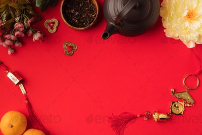 top view of oriental decorations, tangerines, flowers and tea set isolated on red