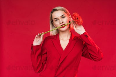 attractive girl with red gerbera flower in mouth, isolated on red