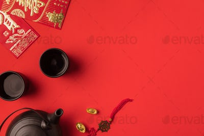 top view of oriental tea set, golden ingots and greeting cards with calligraphy isolated on red