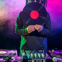 professional african american club DJ with vinyl and sound mixer in nightclub