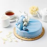 blue tasty cake on chopping board with tea and flower isolated on white
