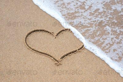 heart shape sign erasing by sea wave on sandy beach