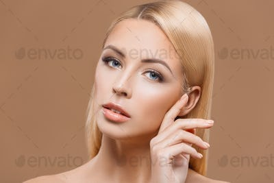 portrait of attractive blonde woman with perfect skin, isolated on brown
