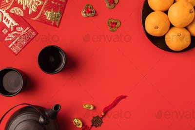 top view of oriental decorations, ingots and ceramic tea set isolated on red