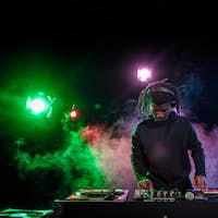 professional african american club DJ in headphones with sound mixer in nightclub