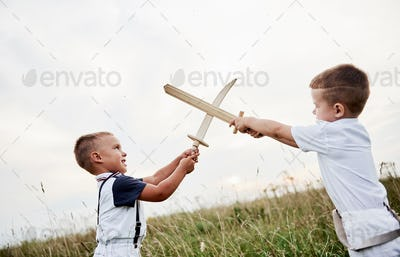 Crossed swords. Like in the movie. Two kids having fun playing with wooden swords in the field