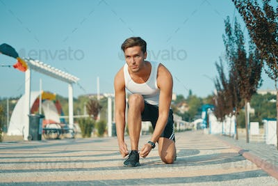Determined young male runner getting ready to start running