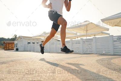 Close up of urban runner's legs run on the street