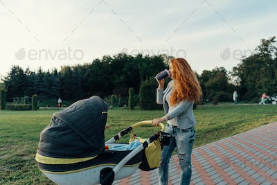 Young mother walking with her child in the morning while drinkin