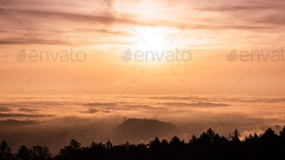 Panorama of Graz city in Styria on autumn morning during sunraise above fog