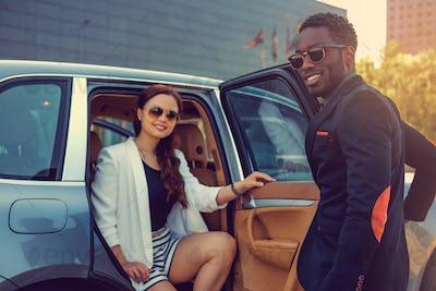 Casual couple posing near a car.