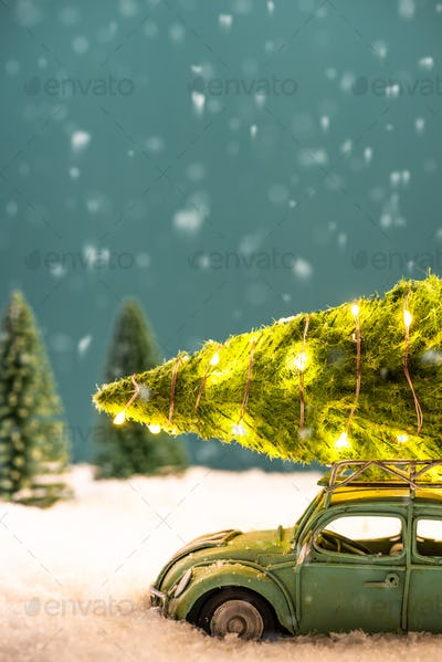Festive Greeting Card. Toy Car Carry Illuminated Christmas Tree on Roof in Snow