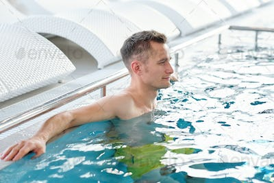 Young handsome relaxed man standing in blue transparent water of swimming pool