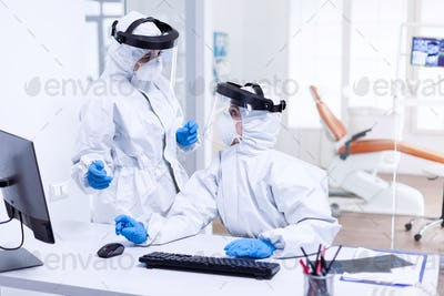 Dentist doctor in ppe suit discussing with nurse