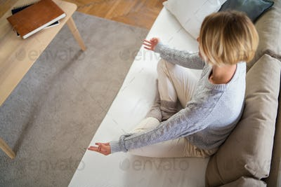 Top view of woman indoors at home doing yoga, mental health and meditation concept.