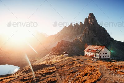 Dazzling angle. Sunset over the Paternkofel mountain with a buildings and little lake in front