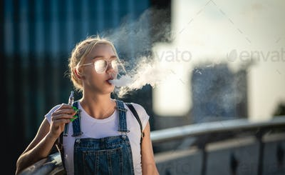 Young woman outdoor vaping e-cigarette on modern city buildings background