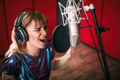 Female with microphone recording a voice for dubbing in music studio