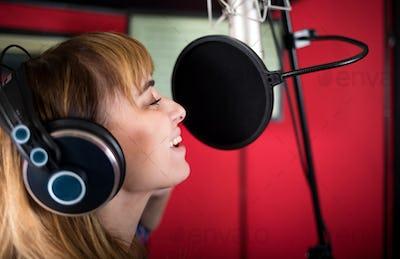 Pretty female singer recording voice in sound studio