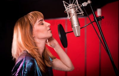 Young singer woman during music session at recording studio