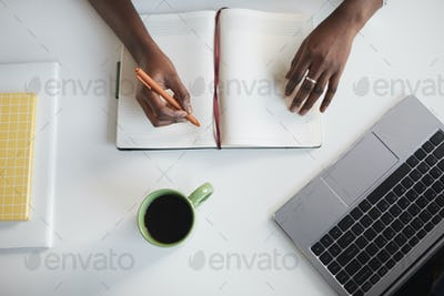 African-American Woman Writing at Desk Top View
