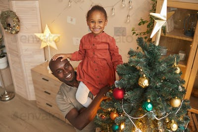 Father and Daughter Decorating Christmas Tree Together
