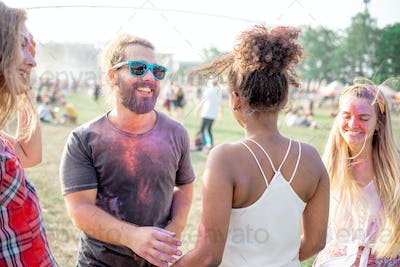 Cheerful friends with color paint on bodies dancing at holi festival